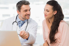 Male doctor showing something on laptop to patient Royalty Free Stock Image