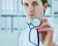 Male doctor showing stethoscope for checkup. Doctor with stethoscope in hand on hospital background for medical visit. Royalty Free Stock Photos