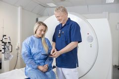 Male Doctor Showing Tablet Computer To Patient At MRI Machine Royalty Free Stock Photo