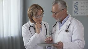 Male doctor showing tablet to his female colleague, electronic medical history. Stock footage stock footage