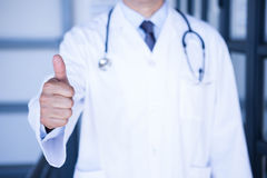 Male doctor showing thumbs up. Close-up of male doctor showing thumbs up in hospital Royalty Free Stock Photography