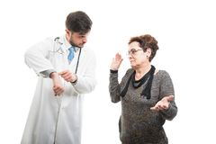 Male doctor showing wrist watch to female senior patient. Like late concept isolated on white background Royalty Free Stock Images