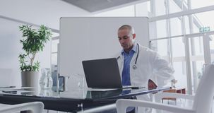 Male doctor sitting at a desk in office 4k stock video