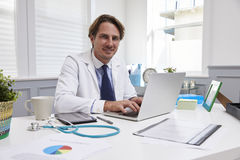 Male Doctor Sitting At Desk Working At Laptop In Office Stock Photography