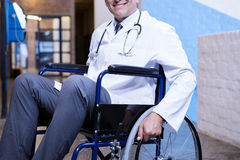 Male doctor sitting on wheel chair Royalty Free Stock Photography