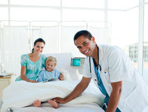 Male doctor smiling at the camera. While examining a patient Stock Image