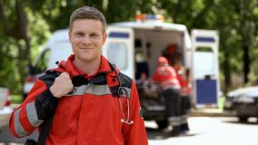 Male doctor smiling into camera, ambulance crew working, blurred on background stock photography