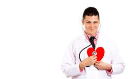 Male doctor smiling and listening to a heart with his stethoscope Stock Photo