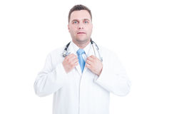 Male doctor standing and adjusting necktie with both hands Stock Photos
