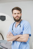 Male Doctor Standing Arms Crossed In Examination Room. Portrait of young male doctor standing arms crossed in examination room Stock Image