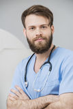 Male Doctor Standing Arms Crossed In Examination Room. Portrait of young male doctor standing arms crossed in examination room Stock Photo