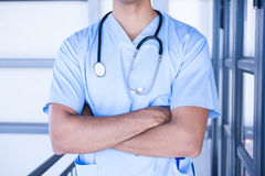 Male doctor standing with arms crossed. In hospital Royalty Free Stock Image