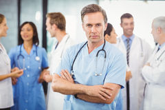 Male doctor standing with arms crossed. Portrait of male doctor standing with arms crossed and colleagues standing behind and discussing in hospital Stock Photography