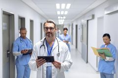 Male doctor standing with digital tablet in corridor at hospital royalty free stock photos
