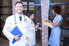 Male doctor standing near library with clipboard. And colleagues standing behind and discussing Stock Image