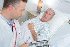 Male doctor standing next to patient and holding results. Male doctor standing next to the patient and holding results Stock Image