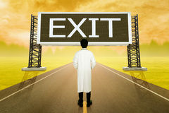 Male doctor standing on road and looking with large sign of exit Royalty Free Stock Photos