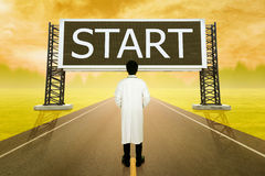 Male doctor standing on road and looking with large sign of star Royalty Free Stock Photo