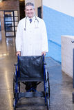 Male doctor standing with wheel chair Stock Photos