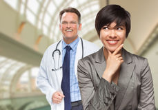 Male Doctor Stands Behind Woman Looking To Side Inside Hospital Royalty Free Stock Photos
