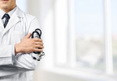 Male doctor with stethoscope on blurred hospital stock photo