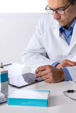 Male doctor with stethoscope at desk using tablet Royalty Free Stock Photography