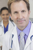 Male Doctor With Stethoscope & Female Colleague Royalty Free Stock Photography