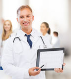 Male doctor with stethoscope showing cardiogram Royalty Free Stock Photo