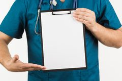 Male doctor with stethoscope writing on clipboard message or boa. Rd, on white background Royalty Free Stock Photo