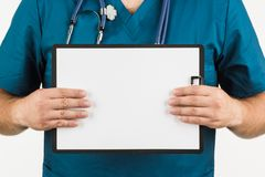 Male doctor with stethoscope writing on clipboard message or boa. Rd, on white background Stock Photos