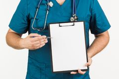 Male doctor with stethoscope writing on clipboard message or boa. Rd, on white background Royalty Free Stock Photos