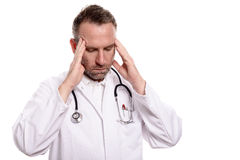 Male doctor suffering from a headache. And fatigue holding his temples with his hands and eyes closed as he grimaces in pain Royalty Free Stock Photos
