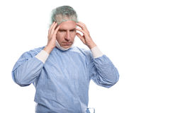 Male doctor suffering from a headache. And fatigue holding his temples with his hands and eyes closed as he grimaces in pain Royalty Free Stock Photo