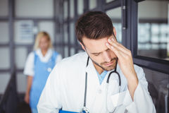 Male doctor suffering from headache. While standing at hospital Royalty Free Stock Image