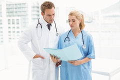 Male doctor and surgeon looking at reports Stock Photos