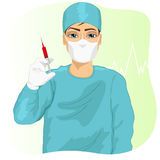 Male doctor, surgeon or nurse in face mask holding a syringe. Male doctor, surgeon or nurse in face mask and scrub suit holding a syringe Stock Photos