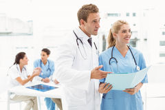 Male doctor and surgeon with reports stock image