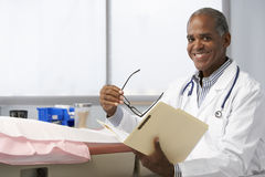 Male Doctor In Surgery Reading Patient Notes Stock Photo