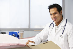 Male Doctor In Surgery Reading Patient Notes Stock Images