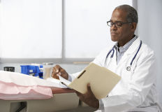Male Doctor In Surgery Reading Patient Notes Royalty Free Stock Photography