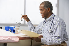 Male Doctor In Surgery Reading Patient Notes Stock Image