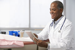 Male Doctor In Surgery Using Digital Tablet Royalty Free Stock Photos