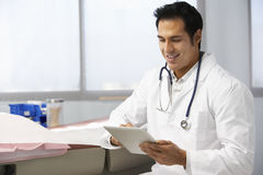 Male Doctor In Surgery Using Digital Tablet Royalty Free Stock Photography