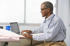 Male Doctor In Surgery Using Laptop Royalty Free Stock Photos