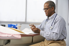 Male Doctor In Surgery Using Mobile Phone Stock Photography