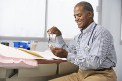 Male Doctor In Surgery Using Mobile Phone Royalty Free Stock Photo