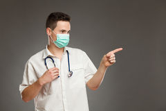 Male doctor in surgical mask pointing. Portrait of a male doctor wearing surgical mask and pointing at copy space. Waist up studio shot on gray background Stock Photography