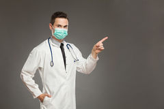 Male doctor in surgical mask pointing. Portrait of a male doctor wearing surgical mask and pointing. Waist up studio shot on gray background Royalty Free Stock Photo