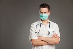 Male doctor in surgical mask. Portrait of a male doctor with arms crossed wearing surgical mask and looking away. Waist up studio shot on gray background Stock Image