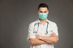 Male doctor in surgical mask. Portrait of a male doctor with arms crossed wearing surgical mask. Waist up studio shot on gray background Stock Photography